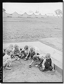 Children playing in sandbox.  Tulare migrant labor camp. Visalia, CA.  1940.  Photographer:  Arthur Rothstein.  Library of Congress.